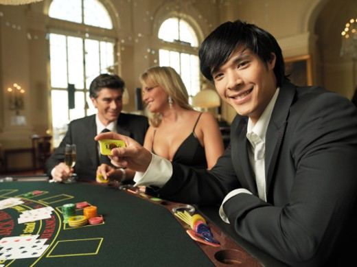 Stock Photo: 1672R-2132 Man holding chip at black jack table, smiling portrait