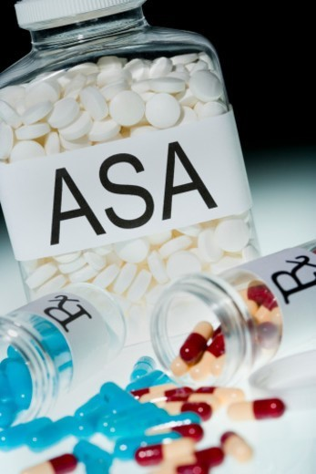 Bottle of aspirin and coloured pills, close-up : Stock Photo