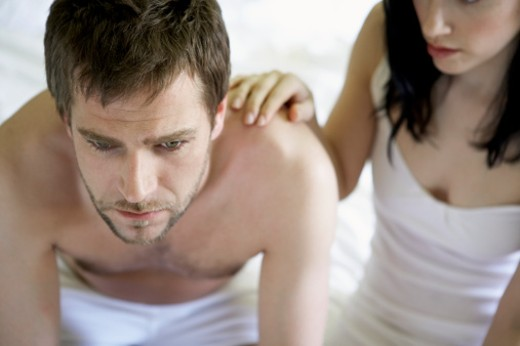 Stock Photo: 1672R-21996 Young couple sitting at edge of bed, man worried, high angle view