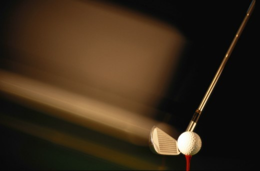 Golf club iron swinging towards ball on tee (blurred motion) : Stock Photo
