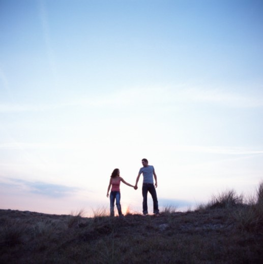 Young couple on sand dune, holding hands : Stock Photo