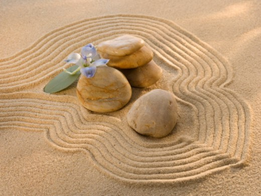 Stock Photo: 1672R-22613 Arrangement of stones and flower on sand