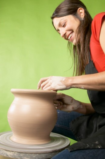 Woman making vase on pottery wheel, smiling, low angle, side view : Stock Photo