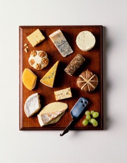 Selection of cheeses on cheeseboard, overhead view : Stock Photo