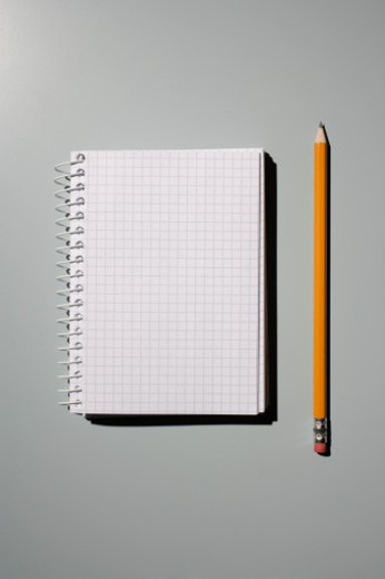Stock Photo: 1672R-23519 Note pad and pencil on gray background, studio shot