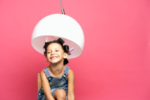 Girl (4-5) playing hairdressing with head under lamp : Stock Photo