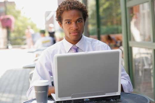 Stock Photo: 1672R-23790 Businessman using laptop at outdoor cafe, portrait