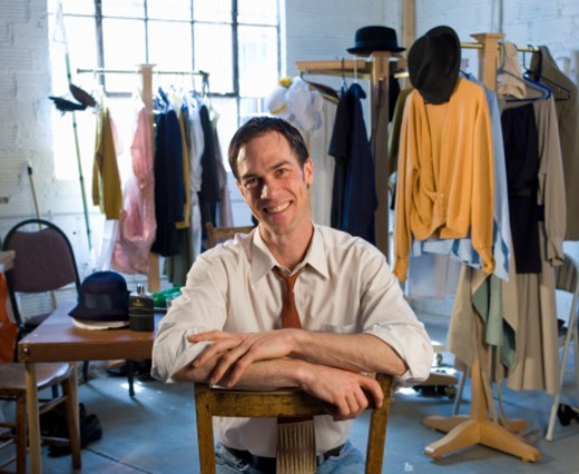 Man sitting in clothing studio, portrait : Stock Photo