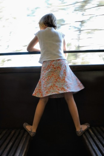 Girl (6-7) looking out window of speeding train, rear view : Stock Photo