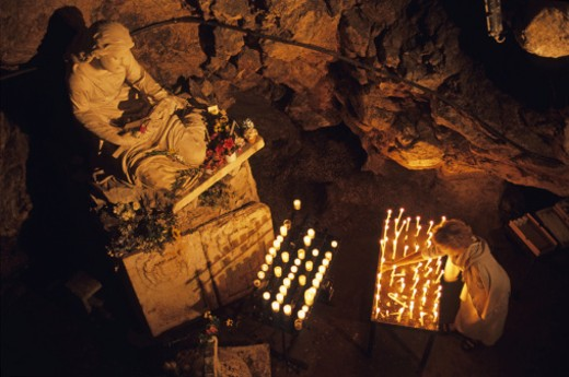 France, Provence, Sainte-Baume Mountain, woman burning candle at Troglodyte Sainte-Marie Madeleine Holy Cave : Stock Photo