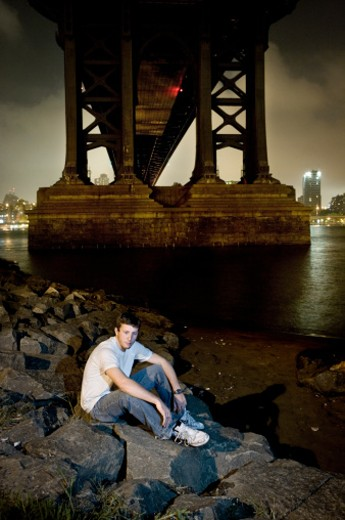 USA, New York City, young man sitting on river bank under Brooklyn bridge at night : Stock Photo