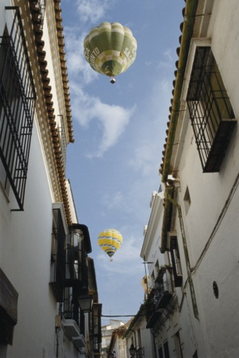 Hot air balloon floating above narrow street, low angle view : Stock Photo