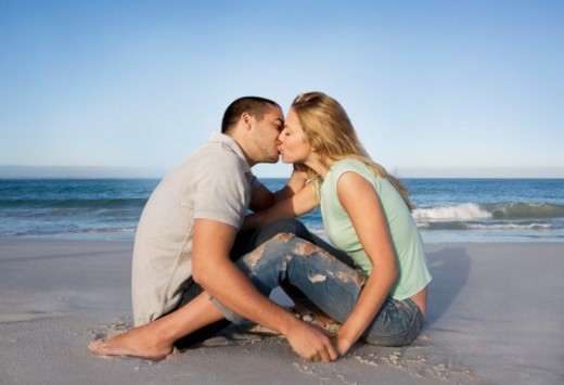 Young couple kissing on beach, side view : Stock Photo