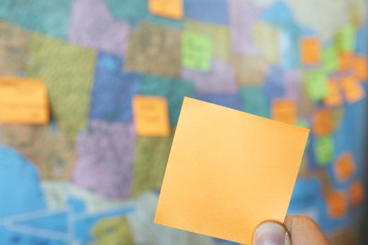 Stock Photo: 1672R-27880 Man holding adhesive note in front of wall map of USA, close-up of note