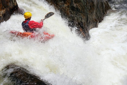 Man kayaking into waterfall, rear view, elevated view : Stock Photo