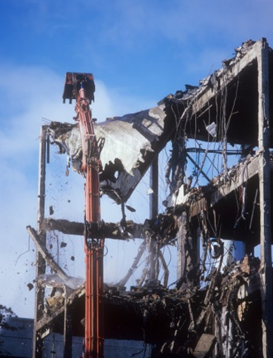 Section of partly demolished building with demolition crane : Stock Photo