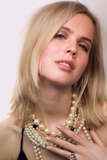 Young woman wearing pearl jewelry, close-up : Stock Photo