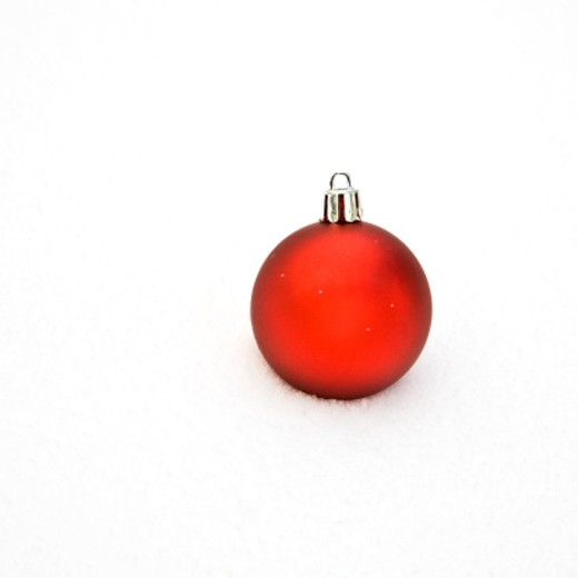 Red Christmas ornament sitting in snow : Stock Photo