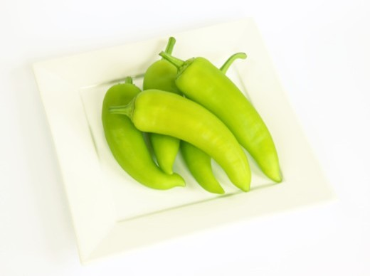 Stock Photo: 1672R-30902 Hungarian green hot wax chilli peppers piled on square white plate with white background.