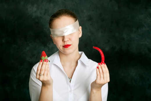 Stock Photo: 1672R-31037 Blindfolded woman holding a chili and strawberry