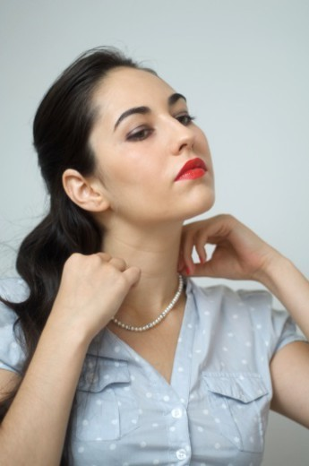 A young woman is looking quite vain while playing with her necklace : Stock Photo