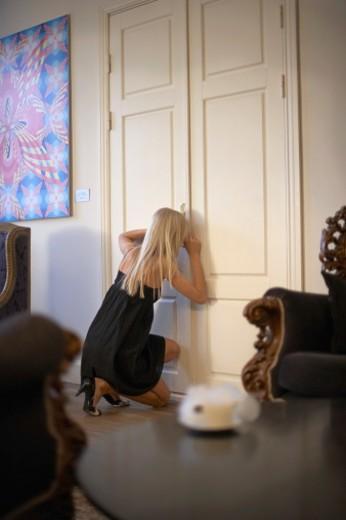 Stock Photo: 1672R-31135 young woman looking thru doorlock