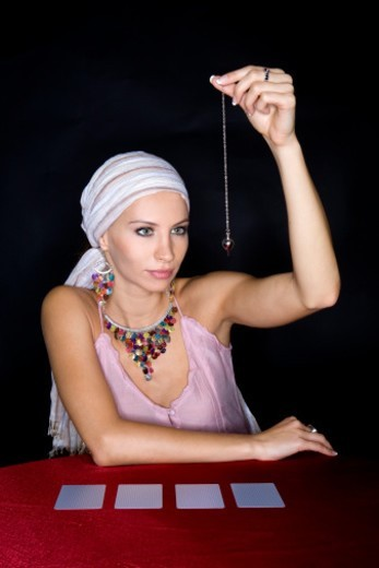 Female fortune teller using pendulum : Stock Photo