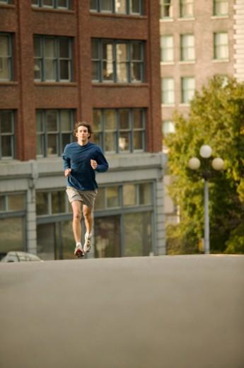 USA, Washington, Seattle, man jogging down street : Stock Photo