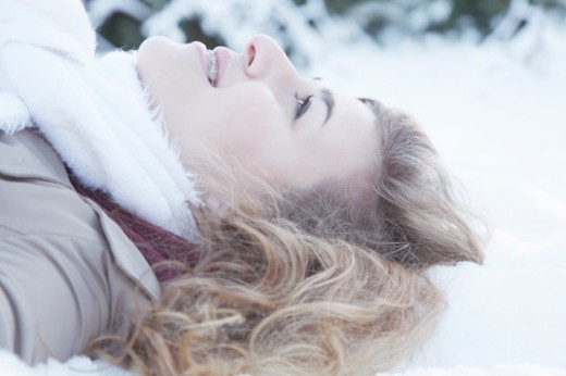 Young woman lying in snow : Stock Photo