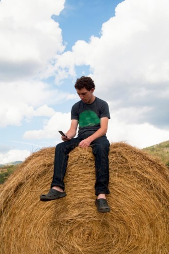 Stock Photo: 1672R-32715 Teenager text messaging from cell phone, sitting on hay bale in field