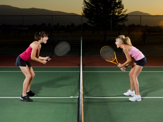Two tennis players face off at the net and scream at each other. : Stock Photo