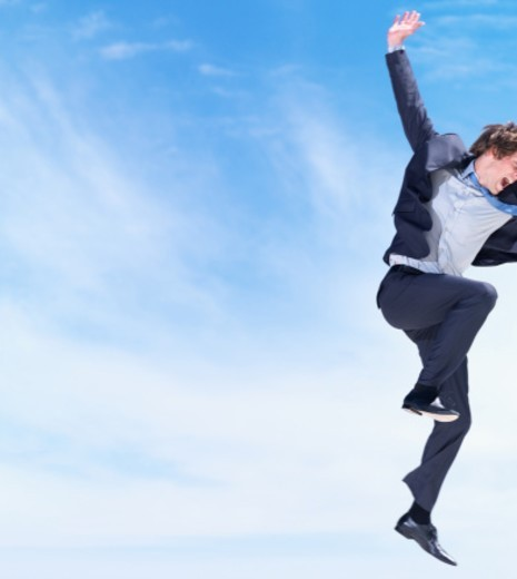 Excited young business man jumping in air with joy against the blue sky : Stock Photo