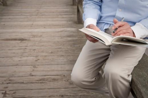 Stock Photo: 1672R-36025 man reading book on boardwalk