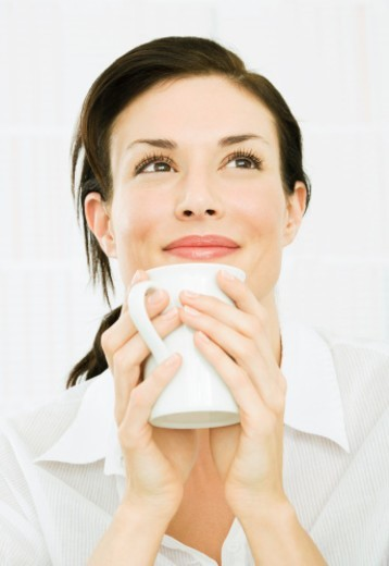 Woman holding cup, smiling, close-up : Stock Photo