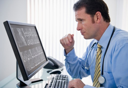 Doctor looking at X-Ray on computer screen : Stock Photo