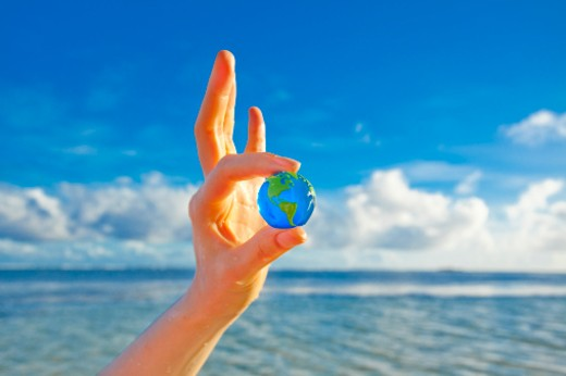 Woman holding mini glass globe in the beach. : Stock Photo