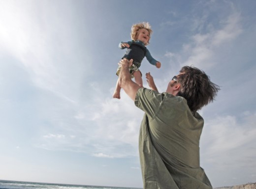 Stock Photo: 1672R-37450 Father playing with son on the beach