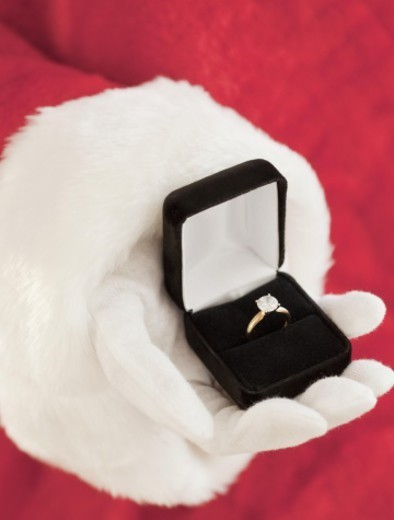 Santa Claus holding out engagement ring : Stock Photo