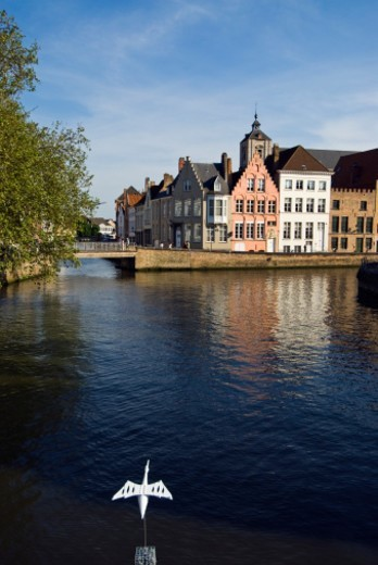 Canal with traditional houses and sculpture of white bird, Belgium, Bruges : Stock Photo