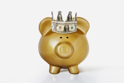 a fat and happy golden piggy bank wears a crown of dollars : Stock Photo