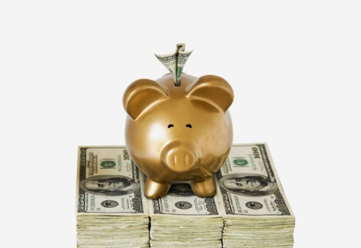 A golden piggy bank sits atop a pile of hundred dollar bills : Stock Photo