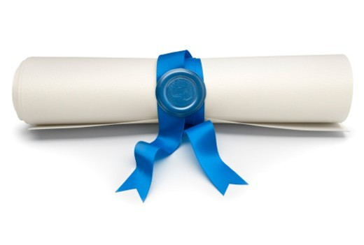A rolled parchment scroll tied with a blue ribbon and secured with a traditional wax seal : Stock Photo