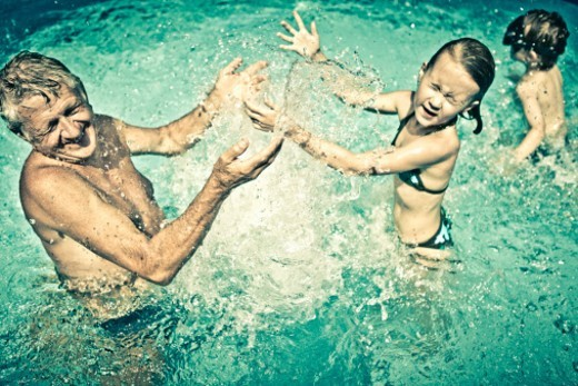 Grandfather playing with his grandchildren, pool : Stock Photo