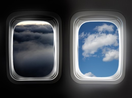 Two windows in plane, one stormy , the other clear : Stock Photo