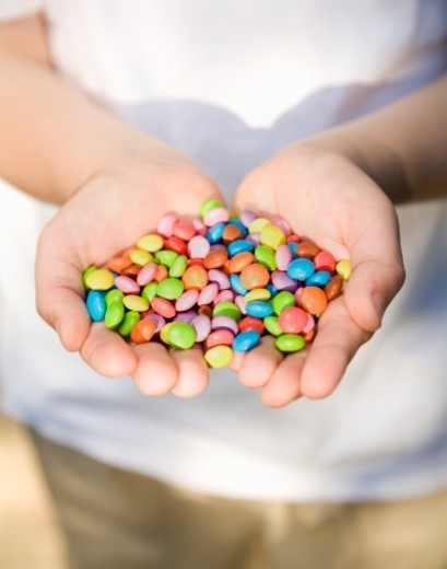 Stock Photo: 1672R-39668 Child's hands holding pile of colourful sweets