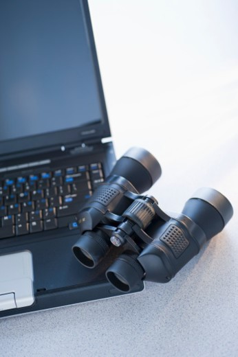 Binoculars on laptop : Stock Photo