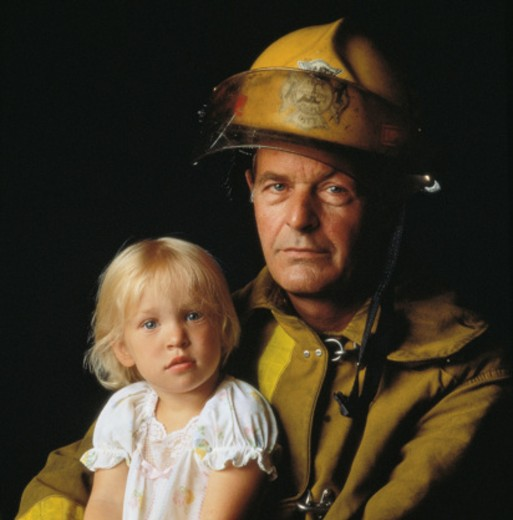 Fireman holding girl (4-6), portrait : Stock Photo
