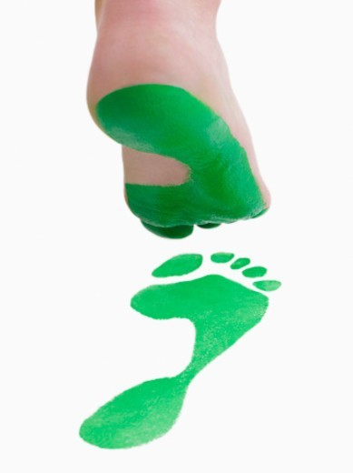 Foot creating green footprint : Stock Photo