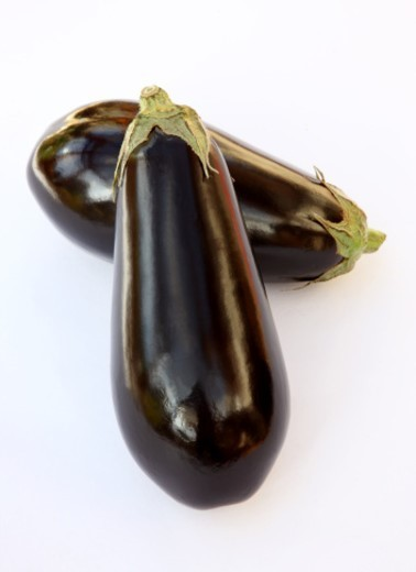 Stock Photo: 1672R-40352 Two fresh, ripe organic aubergines on a white background.