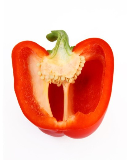 Ripe, red bell pepper cut in half to reveal seeds inside, on a white background : Stock Photo